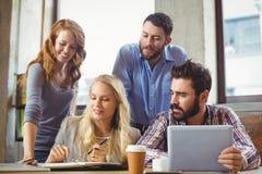 Бизнесмены работая пока обсуждающ в офисе Стоковое Изображение
