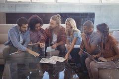Бизнесмены работая пока сидящ совместно на творческом офисе Стоковая Фотография