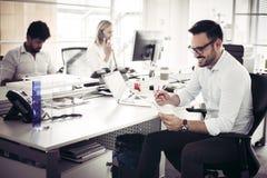 Бизнесмены работая бизнесмены совместно в офисе Стоковые Фото