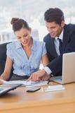Бизнесмены работая совместно и усмехаясь Стоковая Фотография