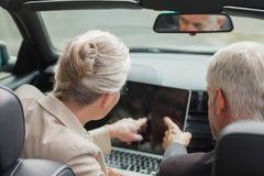 Бизнесмены работая совместно на компьтер-книжке в первоклассном cabriolet Стоковые Фото