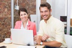 Бизнесмены работая совместно на компьтер-книжке и усмехаться Стоковое Фото