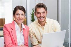 Бизнесмены работая совместно на компьтер-книжке и усмехаться Стоковое фото RF
