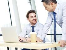 Бизнесмены работая совместно на портативном компьютере Стоковые Изображения RF