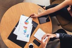 2 бизнесмены работая с диаграммами вокруг таблицы Стоковые Фотографии RF