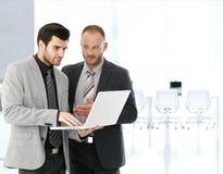 Бизнесмены работая с компьтер-книжкой в конференц-зале Стоковая Фотография