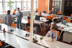 2 бизнесмены работая с компьтер-книжкой в офисе Стоковые Изображения