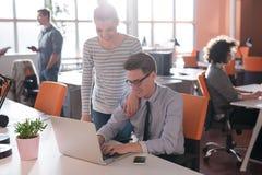 2 бизнесмены работая с компьтер-книжкой в офисе Стоковая Фотография RF