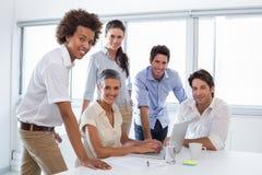 Бизнесмены работая с компьтер-книжкой и усмехаясь на камере Стоковые Изображения
