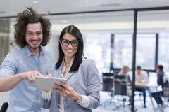 Бизнесмены работая с таблеткой в startup офисе Стоковое Изображение RF