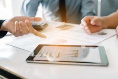 Бизнесмены рассматривая финансовые отчеты работая на столе и Стоковая Фотография RF