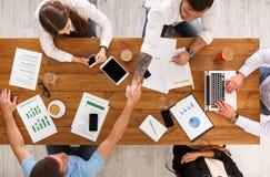 Бизнесмены рукопожатия в офисе, взгляд сверху группы Стоковые Изображения RF