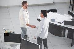 Бизнесмены рукопожатия около настольного компьютера Стоковые Фотографии RF