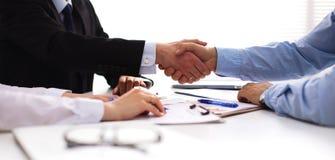 Бизнесмены рукопожатия, сидя на таблице Стоковая Фотография RF