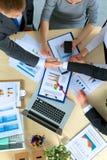 Бизнесмены рукопожатия, сидя на таблице Стоковые Фото