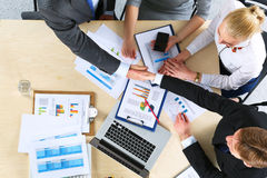 Бизнесмены рукопожатия, сидя на таблице Стоковое Изображение RF