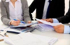 Бизнесмены рукопожатия, сидя на таблице Стоковое Изображение