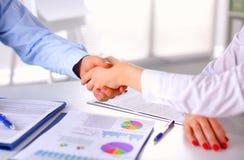 Бизнесмены рукопожатия, сидя на таблице Стоковые Фотографии RF