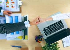 Бизнесмены рукопожатия, сидя на таблице Стоковая Фотография