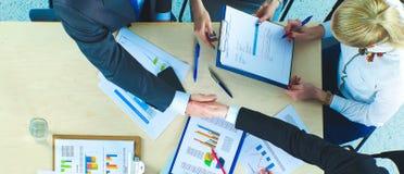 Бизнесмены рукопожатия, сидя на таблице Стоковые Изображения RF