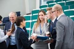 Бизнесмены связывая в лекционном зале Стоковое Фото