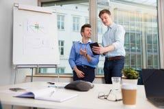 Бизнесмены связывая над таблеткой цифров против окна Стоковое Фото