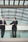 Бизнесмены связывая пока стоящ против прокладывать рельсы Стоковое фото RF