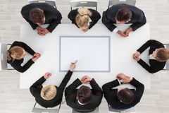 Бизнесмены сидя вокруг пустой таблицы Стоковые Изображения