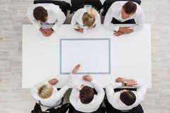 Бизнесмены сидя вокруг пустой таблицы Стоковое фото RF