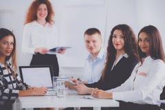 Бизнесмены сидя и обсуждая на деловой встрече, в офисе вектор людей jpg иллюстрации дела Стоковое Изображение RF