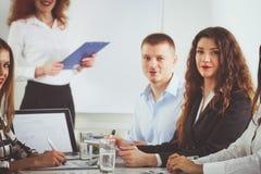 Бизнесмены сидя и обсуждая на деловой встрече, в офисе вектор людей jpg иллюстрации дела Стоковое Фото