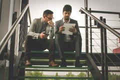 Бизнесмены сидя на лестницах Бизнесмены имея conve Стоковые Фото