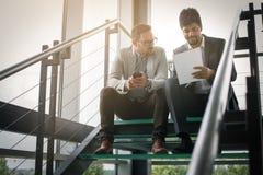 Бизнесмены сидя на лестницах Бизнесмены имея conve Стоковое фото RF