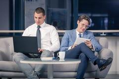 Бизнесмены сидя на софе Стоковая Фотография