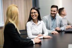 Бизнесмены сидя на таблице Стоковая Фотография