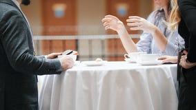 2 бизнесмены сидя таблицей в шведском столе и говоря пока выпивающ кофе сток-видео