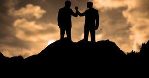 Бизнесмены силуэта держа руки во время захода солнца Стоковые Фото