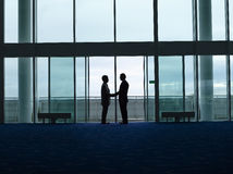 Бизнесмены силуэта тряся руки на авиапорте Стоковое Изображение RF