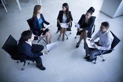 Бизнесмены сидя в круге имея деловую встречу Стоковые Изображения