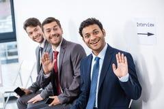 Бизнесмены сидя в очереди и ждать интервью в офисе Стоковая Фотография RF