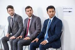 Бизнесмены сидя в очереди и ждать интервью в офисе Стоковые Фотографии RF