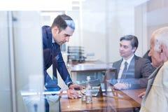 Бизнесмены сидя и коллективно обсуждать на корпоративной встрече Стоковое Изображение RF