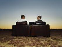 Бизнесмены сидя на креслах с компьтер-книжкой Стоковое Изображение