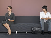 Бизнесмены сидя на софе в зале ожидания Стоковые Изображения RF
