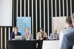 Бизнесмены сидя на столе в зале семинара Стоковые Фото