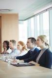Бизнесмены сидя на столе переговоров во время встречи Стоковые Фото
