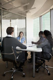 4 бизнесмены сидя на столе переговоров и обсуждая во время деловой встречи Стоковое Изображение