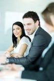 Бизнесмены сидя на столе переговоров Стоковая Фотография