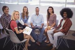 Бизнесмены сидя на стульях во время встречи в творческом офисе Стоковое фото RF