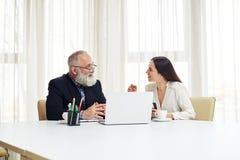 Бизнесмены сидя на таблице и обсуждая новые проекты Стоковые Фото